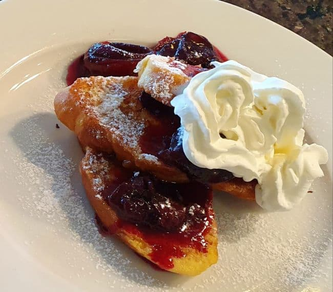 French toast with poached plums and whipped cream
