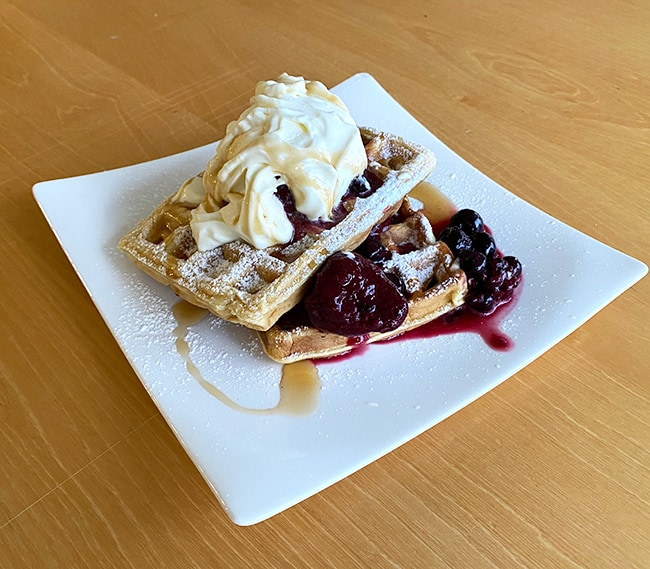 Waffles with plum compote, maple syrup and whipped cream